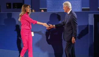 Melania Trump, wife of Republican presidential candidate Donald Trump, left, and former President Bill Clinton, husband of Democratic presidential candidate Hillary Clinton shake hands before the beginning of the second presidential debate at Washington University, Sunday, Oct. 9, 2016, in St. Louis. (AP Photo/ Evan Vucci)