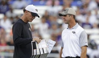 FILE - In this Aug. 3, 2015, file photo, Baltimore Ravens offensive coordinator Marc Trestman, left, speaks with head coach John Harbaugh during NFL football training camp, in Baltimore. The Ravens have fired Marc Trestman as offensive coordinator and replaced him with quarterbacks coach Marty Mornhingweg. Coach John Harbaugh made the move Monday, Oct. 10, 2016, less than 24 hours after the Ravens managed only one touchdown in a 16-10 loss to Washington.(AP Photo/Patrick Semansky, File) **FILE**