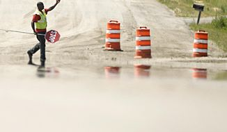 In a July 20, 2016 photo, Philip Kenner directs traffic at a road construction site north of Bismarck as the heat emmenating from the hot pavement creates a mirrored image. Millions of dollars in road upgrades have been completed in North Dakota this summer, and state officials say they are hoping to have a bit more time to complete the lion's share of the planned work. As of the week of Oct. 3,  about two-thirds of the 193 scheduled projects were completed.  (Mike McCleary/The Bismarck Tribune via AP)