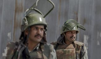 Indian paramilitary soldiers stand guard at an temporary checkpoint during curfew in Srinagar, Indian-controlled Kashmir, Monday, Oct. 10, 2016. Authorities in Indian portion of Kashmiri imposed restrictions in some parts of Srinagar fearing religious processions marking the Muslim month of Muharram would turn into anti-India protests. (AP Photo/Dar Yasin)