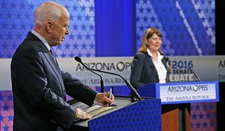 Incumbent Republican Sen. John McCain, left, takes a few notes as Arizona Democratic Rep. Ann Kirkpatrick speaks to the debate moderators prior to their only scheduled debate Monday, Oct. 10, 2016, in Phoenix before next month's general election. (AP Photo/Ross D. Franklin)
