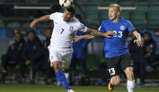 Greece's Nikolaos Karelis, left, and Estonia's Taijo Teniste struggle for a ball during their World Cup Group H qualifying soccer match between Estonia and Greece in Tallinn, Estonia, on Tuesday, March 29, 2016. (AP Photo/Liis Treimann)
