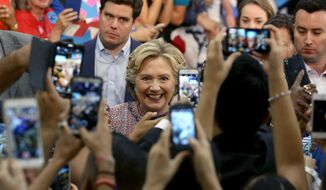Democratic presidential candidate Hillary Clinton poses for photos after speaking at a rally at Miami Dade College in Miami, Tuesday, Oct. 11, 2016. (Mike Stocker/South Florida Sun-Sentinel via AP)