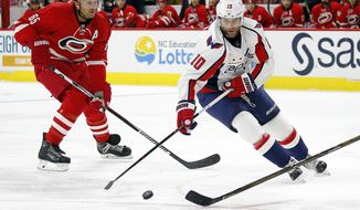 Washington Capitals' Brett Connolly (10) moves the puck past Carolina Hurricanes' Ron Hainsey (65) during the first period of an NHL hockey game in Raleigh, N.C., Friday, Oct. 7, 2016. (AP Photo/Karl B DeBlaker)