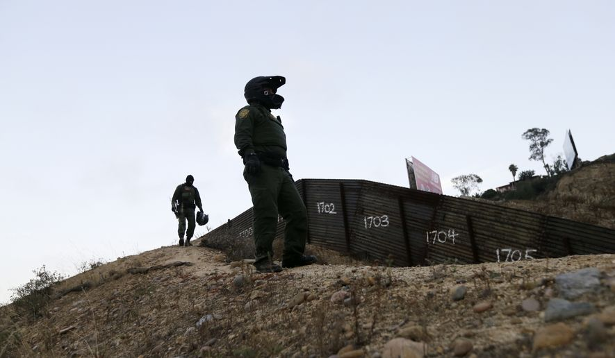Border Patrol agents look over the primary fence separating Tijuana, Mexico, and San Diego on June 22, 2016. (Associated Press) **FILE**