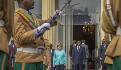 German Chancellor Angela Merkel, center-left, and Ethiopia's Prime Minister Hailemariam Desalegn, center-right, inspect the honor guard at the national palace in Addis Ababa, Ethiopia Tuesday, Oct. 11, 2016. Merkel is visiting Ethiopia, where her meeting with Prime Minister Hailemariam  Desalegn is expected to focus on the country's newly declared state of emergency, after months of protests demanding wider freedoms, and other issues including migration. (AP Photo/Mulugeta Ayene)