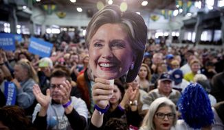 A member of the audience holds up a mask depicting Democratic presidential candidate Hillary Clinton as she speaks at a rally at the Colorado State Fairgrounds in Pueblo, Colo., Wednesday, Oct. 12, 2016, to attend a rally. (AP Photo/Andrew Harnik)