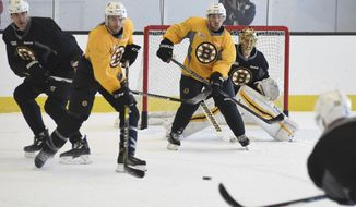 Boston Bruins defenseman Zdeno Chara, left, starts to drop his stick on a shot to goalie Tuukka Rask, right, during an NHL hockey practice in Boston, Tuesday, Oct. 11, 2016.  At right is left wing Brad Marchand.  From left are Chara, center Patrice Bergeron, left wing Brad Marchand and Rask. (Faith Ninivaggi/The Boston Herald via AP)