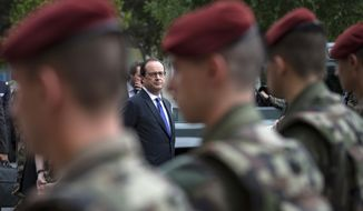 FILE - In this July 25, 2016 file photo, French president Francois Hollande reviews troops at the army base and command centre for France's anti-terror 'Vigipirate' plan, dubbed 'Operation Sentinelle', in Vincennes, outside Paris. France's government has approved Wednesday Oct. 12, 2016 a decree creating a National Guard to bolster security against extremist attacks across the country. The Guard, which is expected to reach 84,000 people by 2018, is a new, enhanced version of the existing reserve forces. (Ian Langsdon/Pool Photo via AP, File)