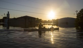 Buckley Miller paddles a canoe past a flooded water treatment plant  in downtown Lumberton after Hurricane Matthew caused downed trees, power outages and massive flooding along the Lumber River Tuesday, Oct. 11, 2016 in Lumberton, NC. (Travis Long/The News & Observer via AP)
