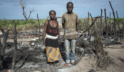 In this photo provided by International Rescue Committee, a mother and her son stand amid the ashes of their hut and personal possessions in the Kaga Bandoro refugee camp in Central African Republic, Thursday, Oct. 13, 2016. Fighters with the former Seleka rebel group attacked a northern town in Central African Republic overnight Wednesday, and clashes left at least 30 dead and 57 wounded as United Nations peacekeepers confronted them, the U.N. said. The attack in Kaga-Bandoro was likely retaliation for the death on Tuesday of a suspected former Seleka member, the peacekeeping mission said in a statement. Peacekeepers repelled the attackers, killing at least 12 of them, the U.N. mission said. (David Belluz/International Rescue Committee via AP)