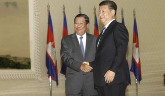Cambodian Prime Minister Hun Sen, left, shakes hands with  Chinese President Xi Jinping, right, before a meeting at the Peace Palace, in Phnom Penh, Cambodia, Thursday, Oct. 13, 2016. Xi is on a state visit to strengthen the relationships between the two countries and to witness the agreements to be signed. (AP Photo/Heng Sinith)