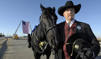 Deputy Hill Goedhart leads the riderless horse Max that belonged to Lancaster sheriff's Deputy Steve Owen before a memorial service on Thursday, Oct. 13, 2016 in Lancaster, Calif. Owen, a 29-year sheriff's veteran, was shot on Oct. 5 as he answered a report of a burglary at an apartment building in the city north of Los Angeles.    (John McCoy/Los Angeles Daily News via AP)