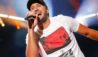 FILE - In this June 12, 2016 file photo, Luke Bryan performs at the CMA Music Festival in Nashville, Tenn. The country singer is in currently performing in his Farm Tour, where he brings concerts to working farms in small agriculturally-focused communities and cities throughout the South and Midwest. (Photo by Al Wagner/Invision/AP, File)