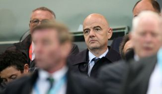 FIFA President Gianni Infantino, centre, watches from the stands during the 2018 World Cup Qualifying soccer match, Northern Ireland versus San Marino, at Windsor Park, Belfast, Northern Ireland, Saturday Oct. 8, 2016. (Brian Lawless/PA via AP)