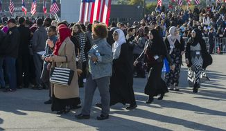 Supporters of Democratic presidential candidate Hillary Clinton file into Burke Lakefront Airport in Cleveland, Friday, Oct. 14, 2016, for a campaign appearance by President Barack Obama in support of Clinton. (AP Photo/Phil Long)