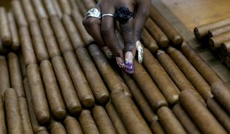 This March 1, 2013, file photo shows a worker selecting cigars at the H. Upmann cigar factory, where people can take tours as part of the 15th annual Cigar Festival in Havana, Cuba. The Obama administration announced Friday, Oct. 14, 2016, it is eliminating a $100 limit on the value of Cuban rum and cigars that American travelers can bring back from the island. (AP Photo/Ramon Espinosa, File)