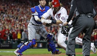 Washington Nationals' Jayson Werth is tagged out at home by Los Angeles Dodgers catcher Yasmani Grandal during the sixth inning during Game 5 of a baseball National League Division Series, at Nationals Park, Thursday, Oct. 13, 2016, in Washington, as home plate umpire Jeff Kellogg watches. The Dodgers won 4-3. (AP Photo/Alex Brandon)
