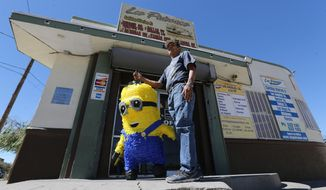 Juan Vega carries a Minion pinata to a bus station near the entrance to Chihuahuita on Oct. 4, 2016 in El Paso, Texas.  The Segundo Barrio and Chihuahuita neighborhoods in South El Paso were added to the National Trust for Historic Preservation's list of America's 11 Most Endangered Historic Places, a list that seeks to bring national attention to places with rich architectural and cultural heritage that might be facing demolition. (Victor Calzada/The El Paso Times via AP)