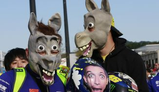 Japanese fans of Valentino Rossi, wearing horse mask, wait for Rossi before a free practice session for the MotoGP Japanese Motorcycle Grand Prix at the Twin Ring Motegi circuit in Motegi, north of Tokyo, Friday, Oct. 14, 2016. (AP Photo/Shizuo Kambayashi)