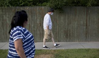 """ADVANCE FOR THE WEEKEND OF OCT. 15-16 AND THEREAFTER - In an Aug. 21, 2016 photo, Steve Bailey wears a mask outside of his house while he attempts to go for a walk around the block with is wife in Provo, Utah. Steve went through the lung transplant for his two children. """"They need their father to live,"""" he said.  Steve, who has a rare genetic disorder known as Alpha-1 deficiency, received the lungs only a few months prior after struggling with oxygen tanks and breathing problems for years.  (Sammy Jo Hester/Daily Herald via AP)"""