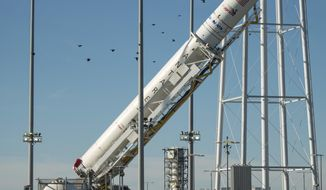 In this photo released by NASA, the Orbital ATK Antares rocket, with the Cygnus spacecraft onboard, is raised into the vertical position on launch Pad-0A, Friday, Oct. 14, 2016, at NASA's Wallops Flight Facility in Virginia. Two years after a launch explosion, the space company Orbital ATK is returning to Virginia to send a load of supplies to the International Space Station. A planned nighttime launch this weekend from Wallops Island on Virginia's Eastern Shore will be visible along parts of the coast if the skies are clear. Liftoff is scheduled on Sunday .(Bill Ingalls/NASA via AP)