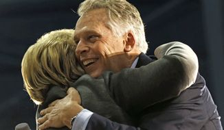 This Monday Feb. 29, 2016, file photo shows Virginia Gov. Terry McAuliffe, right, as he hugs Democratic presidential candidate Hillary Clinton as she arrives to speak at a campaign rally in Norfolk, Va. (AP Photo/Gerald Herbert) ** FILE **