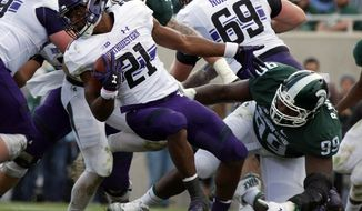 Northwestern's Justin Jackson (21) spins away from Michigan State's Raequan Williams (99) during the second quarter of an NCAA college football game, Saturday, Oct. 15, 2016, in East Lansing, Mich. (AP Photo/Al Goldis)