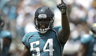 FILE - In this Sept. 20, 2009, file photo, Jacksonville Jaguars defensive end Quentin Groves (54) acknowledges the fans in the first half of an NFL football game against Arizona Cardinals in Jacksonville, Fla Groves, who played defensive end for Auburn from 2004-07 and shares the program record for sacks, died in his sleep while visiting Trinidad, his wife's native country, Auburn spokesman Kirk Sampson said Saturday, Oct. 15, 2016. He was 32. Sampson said he didn't know the cause of death. AP Photo/John Raoux, File)