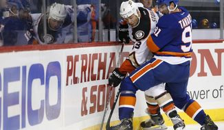 CORRECTS TO SECOND PERIOD NOT FIRST New York Islanders center John Tavares (91) pins Anaheim Ducks defenseman Clayton Stoner (3) against the boards during the second period of an NHL hockey game, Sunday, Oct. 16, 2016, in New York. (AP Photo/Kathy Willens)