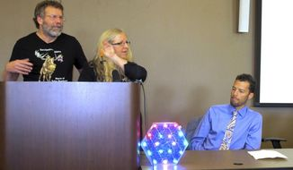 In this Sept. 30, 2016, photo, Solar Roadways founders Scott Brusaw, left, and Julie Brusaw display a one-third sized replica of one of their solar pavement panels at a news conference in Sandpoint, Idaho as Sandpoint mayor Shelby Rognstad looks on at right. Rognstad said the company is drawing visitors to the resort town. Solar Roadways recently unveiled its first public installation in a downtown plaza in the resort town of Sandpoint: about 150 square feet of hexagon-shaped solar panels that people can walk and bicycle on. (AP Photo/Nicholas K. Geranios)