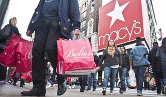 FILE - In this Friday, Nov. 27, 2015, file photo, shoppers carry bags as they cross a pedestrian walkway near Macy's in Herald Square,  in New York. Macy's announced Monday, Oct. 17, 2016, it is staying committed to Thanksgiving Day shopping, confirming that it will open an hour earlier on Thanksgiving Day. The move comes as several stores and a mall operator have decided to close for the turkey feast. (AP Photo/Bebeto Matthews, File)
