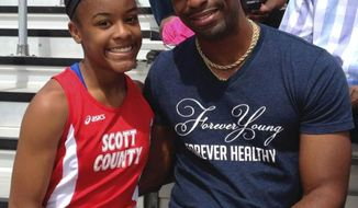 In this May 3, 2014, photo, Trinity Gay, a seventh-grader racing for her Scott County High School team, poses for a photo with her father Tyson Gay, after she won the 100 meters and was part of the winning 4-by-100 and 4-by-200 relays at the meet in Georgetown, Ky. The 15-year-old daughter of Olympic sprinter Tyson Gay was fatally shot in the neck, authorities and the athlete's agent said Sunday, Oct. 16, 2016, and police have arrested a man in connection with the shooting. (Mark Maloney/Lexington Herald-Leader via AP)