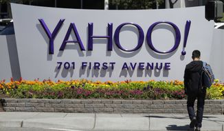 In this Tuesday, July 19, 2016, photo, a man walks in front of a Yahoo sign at the company's headquarters in Sunnyvale, Calif. (AP Photo/Marcio Jose Sanchez)