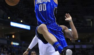 FILE - In this April 1, 2016, file photo, Orlando Magic forward Aaron Gordon gets a slam dunk against the Milwaukee Bucks center Greg Monroe, right, during the first half of an NBA basketball game, in Milwaukee. After being known primarily for his dunks during his first two years in the NBA, Gordon is being asked to make the transition from power forward to what seems his more natural position, small forward. It will be a huge challenge as new Magic coach Frank Vogel is looking for Gordon to be a major scoring threat and shooter in the offense. (AP Photo/Darren Hauck, File)