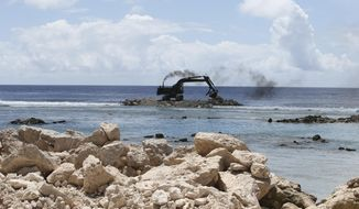 This Nov. 5, 2015, photo shows a heavy earth mover building a sea wall on Majuro Atoll, Marshall. Rising seas in the Marshall Islands can be seen on many of the Atolls in the group as more coastline disappears and vegetation is washed away. The US military ignored warnings about rising seas to build a space radar costing nearly a billion dollars on a tiny atoll in the Marshall Islands. The Space Fence system is considered vital for keeping astronauts and satellites safe by tracking space junk as small as a baseball.(AP Photo/Rob Griffith)