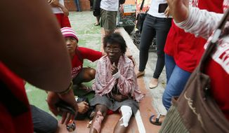 A protester who was run over by a Philippine National Police van waits for an ambulance outside the U.S. Embassy in Manila, Philippines Wednesday, Oct. 19, 2016. A Philippine police van rammed into protesters, leaving several bloodied, as an anti-U.S. rally turned violent Wednesday at the embassy. (AP Photo/Bullit Marquez)