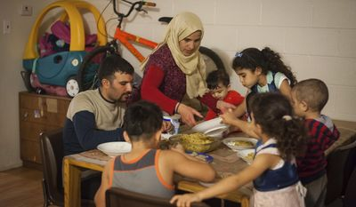 In this Thursday, Sept. 29, 2016 photo, The Al Ali family eats dinner together at their apartment in Crafton Heights, Pa. after father and husband Motab, left, 31, came home from work at UPS. At center top, mother and wife Sabha makes sure their six children get their share. The family was relocated to the U.S. from Syria after four years of living in a refugee camp amid strife in the region. (Stephanie Strasburg  /Pittsburgh Tribune-Review via AP)