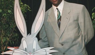 "FILE - In this undated 1995 file photo, Michael Jordan is seen with cartoon character Bugs Bunny during a news conference for ""Space Jam."" Fathom Events and Waner Bros. say the film that combines live action and animation will return to theaters on Nov. 13, 2016, to mark the 20th anniversary of its release. (AP Photo/Marty Lederhandler, File)"