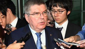 "IOC President Thomas Bach speaks to the media following his meeting with Japanese Prime Minister Shinzo Abe at Abe's official residence in Tokyo Wednesday, Oct. 19, 2016. With Abe, Bach discussed the possibility of staging some Olympic events in the northeastern region of Japan hit by the 2011 tsunami and Fukushima disaster. ""Baseball and softball were some of the options under discussion,"" Bach said. (Yoshinobu Shimizu/Kyodo News via AP)"