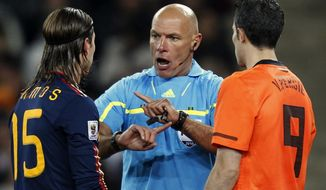 FILE - In this Sunday, July 11, 2010 file photo, referee Howard Webb of England, center, speaks with Spain's Sergio Ramos, left, and Netherlands' Robin van Persie during the World Cup final soccer match in Johannesburg, South Africa. Moments before the start of the most game of his life, Webb had been struck down by another bout of Obsessive compulsive disorder, a condition in which a person has obsessive thoughts and compulsive behavior. Webb kept the condition secret throughout a career that saw him referee the Champions League final and World Cup final in the same year, 2010, fearing the harsh world of soccer would mark him down as mentally unsound. (AP Photo/Luca Bruno, File)