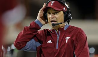 FILE - In this Oct. 24, 2015, file photo, Troy head coach Neal Brown adjusts his headset during the second half of an NCAA college football game against New Mexico State in Las Cruces, N.M. The Troy Trojans have staged a major comeback. A program that hasn't had a winning record since 2010 is on the brink of bowl eligibility, lead the Sun Belt Conference and flirted with an upset of No. 4 Clemson. (AP Photo/Andres Leighton, File)