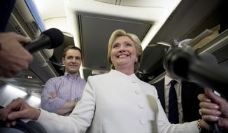 Democratic presidential candidate Hillary Clinton, center, accompanied by Campaign Manager Robby Mook, left, and traveling press secretary Nick Merrill, right, smiles as she speaks with members of the media aboard her campaign plane at McCarran International Airport in Las Vegas, Wednesday, Oct. 19, 2016, following the third presidential debate. (AP Photo/Andrew Harnik)