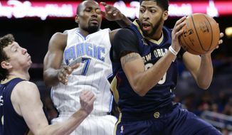 New Orleans Pelicans' Anthony Davis, right, grabs a rebound away from Orlando Magic's Serge Ibaka (7) as teammate Omer Asik, left, comes in to help during the first half of an NBA basketball game, Thursday, Oct. 20, 2016, in Orlando, Fla. (AP Photo/John Raoux)