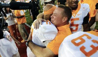 FILE- Int his Oct. 1, 2016, file photo, Tennessee head coach Butch Jones hugs quarterback Joshua Dobbs (11) after defeating Georgia 34-31 in an NCAA college football game in Athens, Ga. Tennessee's bye week came at an ideal spot for the 18th-ranked Volunteers, who need the extra time to get healthy after enduring a four-game stretch against ranked foes. (AP Photo/John Bazemore, File)