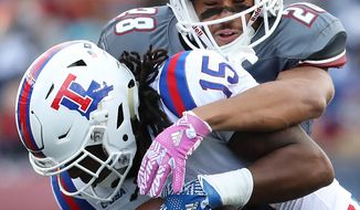 Massachusetts' Jackson Porter stops Louisiana Tech receiver Kam McKnight during the first half of an NCAA college football game Saturday, Oct. 15, 2016, in Foxborough, Mass. (Matthew J. Lee/The Boston Globe via AP)