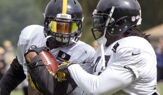 FILE - In this Aug. 13, 2014, file photo, Pittsburgh Steelers running back LeGarrette Blount, right, tries to strip the ball from fellow Steelers running back Le'Veon Bell in a drill during NFL football training camp in Latrobe, Pa. Blount effectively walked out on the Steelers and good friend Le'Veon Bell two years ago due to a lack of playing time. Bell didn't take it personally though Blount is likely to receive a rude welcome when he returns to Pittsburgh on Sunday while playing for New England. (AP Photo/Keith Srakocic, File)