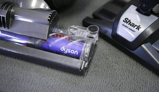 A Dyson, left, and SharkNinja cleaning heads from an upright vacuum are positioned together at the evacuumstore.com retail location in Braintree, Mass., Thursday, Oct. 20, 2016. Dyson and SharkNinja, fierce competitors in the U.S. vacuum cleaner market, have settled a bitter legal dispute. The two companies were to have duked it out in federal court over advertising campaigns in which each claimed their vacuums had the best suction or cleaned better. (AP Photo/Charles Krupa)