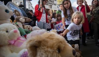 Children join demonstrators in laying teddy bears outside the gates of Downing Stree in central London during a protest to highlight the high numbers of children killed in bombings in Syria and to demand the government intervene over Russian and Syrian bombing campaigns, Saturday, Oct. 22, 2016. (Stefan Rousseau/PA via AP)