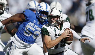 Hawaii quarterback Dru Brown, front, eludes a tackle by Air Force defensive lineman David Harris in the first half of an NCAA college football game, Saturday, Oct. 22, 2016, at Air Force Academy, Colo. (AP Photo/David Zalubowski)